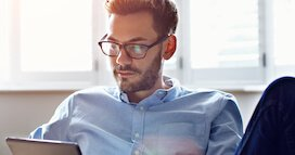 Young Man With Glasses On Computer